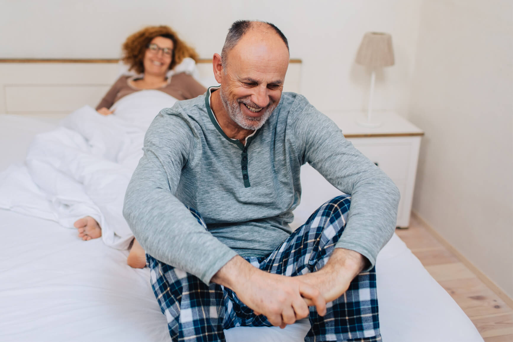 Man bed smiling